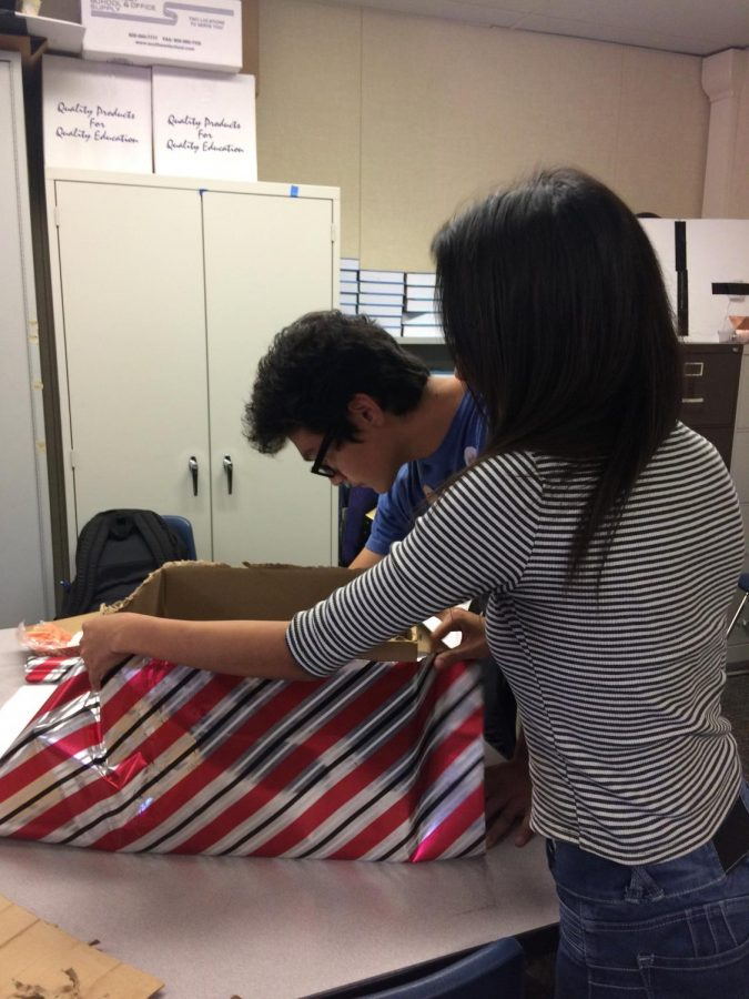 Ana-Teresa Mendoza and Franklin Guevara work on the Pro Pet Project donation boxes.
