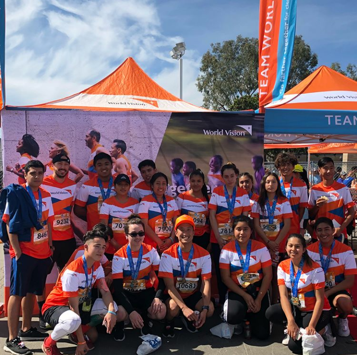 A group picture of the runners at the Team World Vision tent.