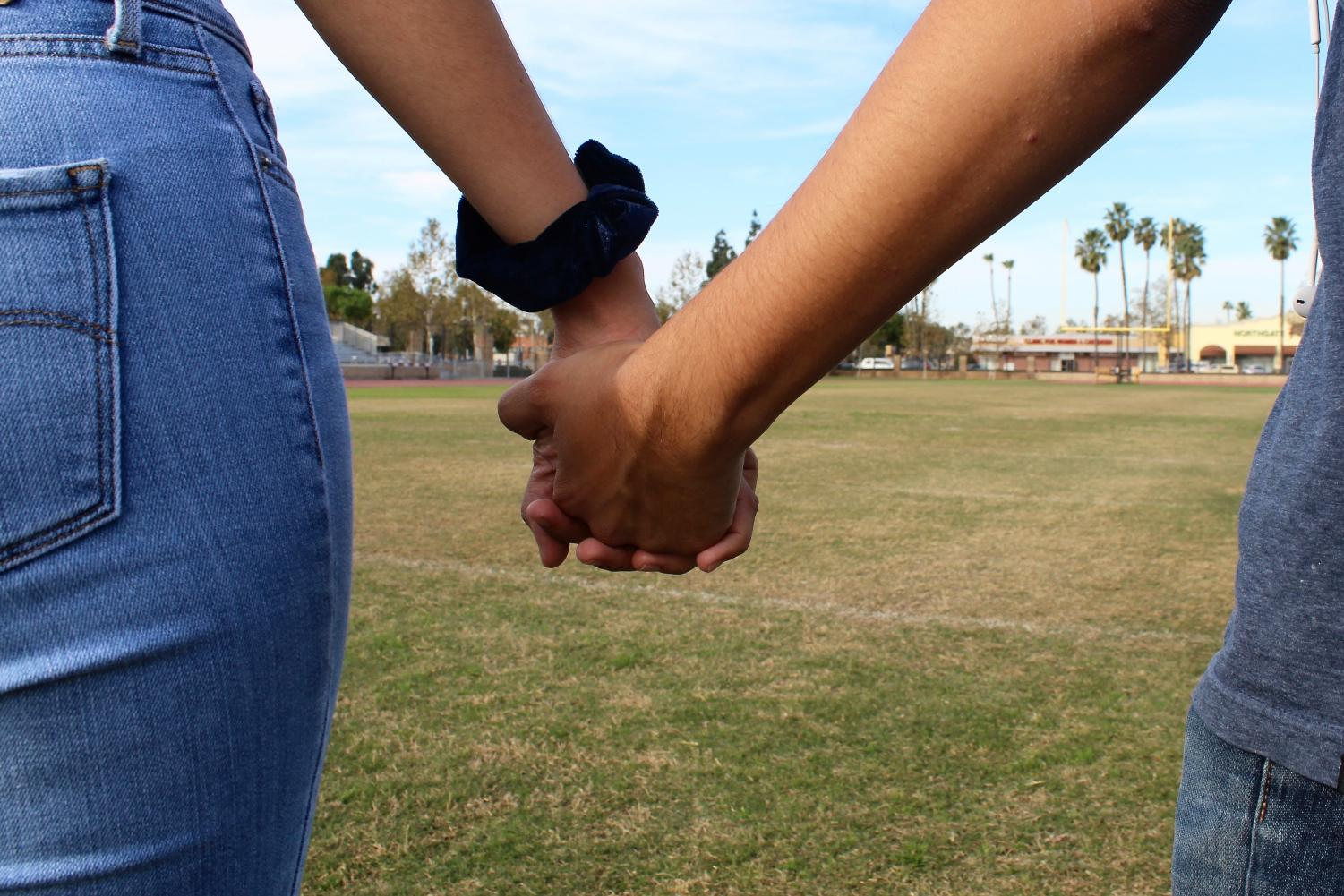 A couple holds hands.