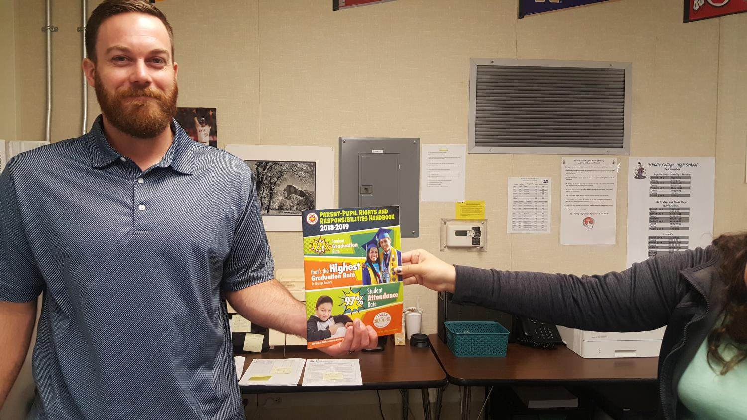 """AVID teacher, Matthew Curtis, hands the """"Parent-Pupil Rights and Responsibilities Handbook"""" to a sophomore student."""
