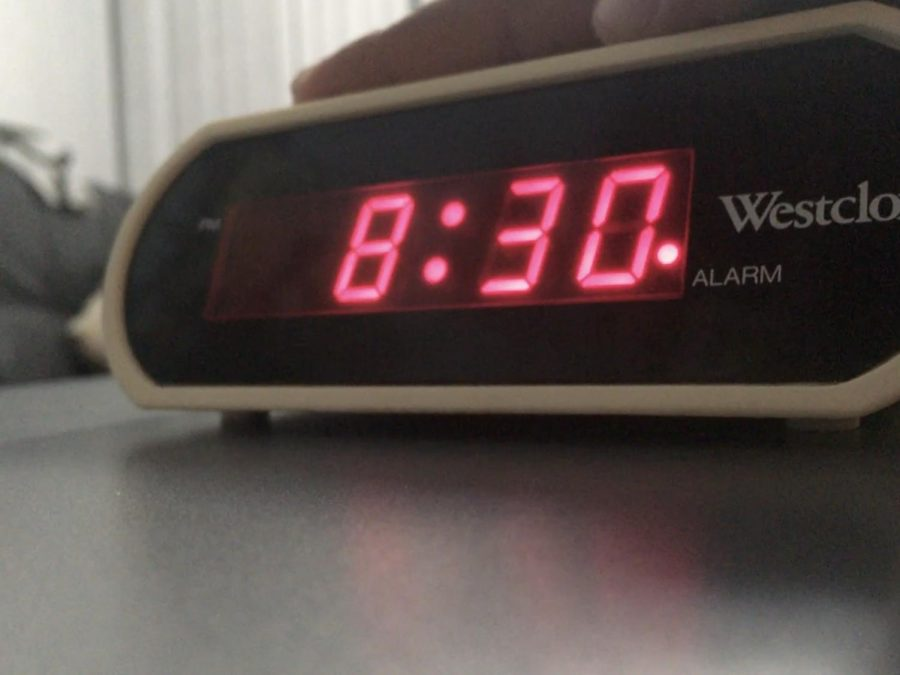 A student snoozes her alarm for the new school day because of the new law.