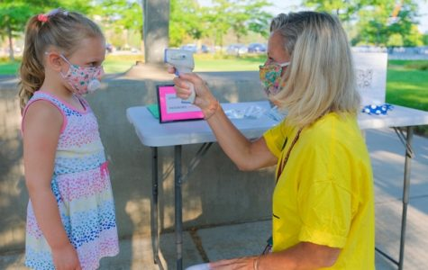 A student gets her temperature checked before being allowed back at school.