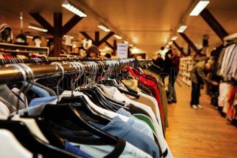 People shuffle through clothing while thrifting.